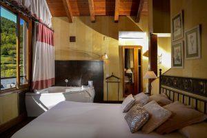 hotel rustico con bañera de hidromasaje en la habitación en Huesca